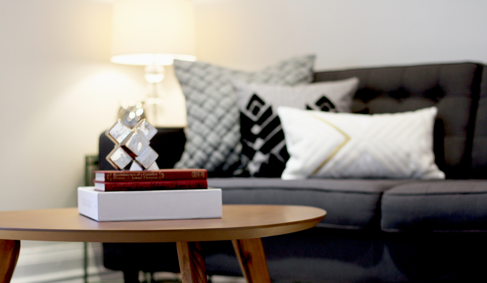 A living room with a wooden coffee table in the foreground with a stack of books on top. Sofa with throw pillows in the background with a side table and illuminated table lamp. Airbnb staging example