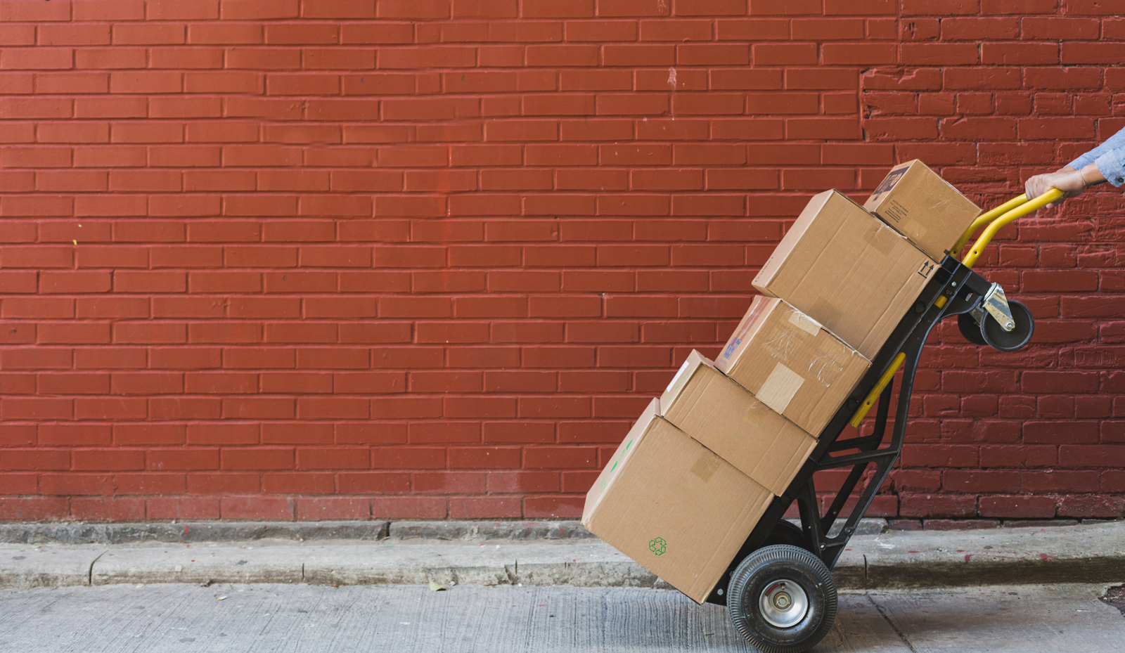 Red brick wall with a stack of moving boxes on a hand cart being pulled.