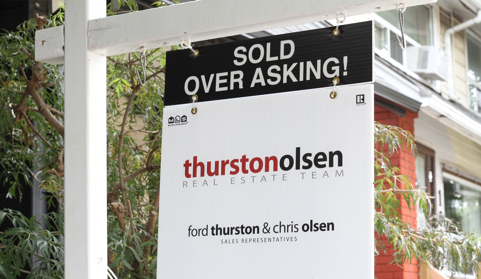White wooden sign post with text: SOLD OVER ASKING! Thurston Olsen Real Estate Team Ford Thurston and Chris Olsen, Sales Representatives. Who pays your real estate agent?