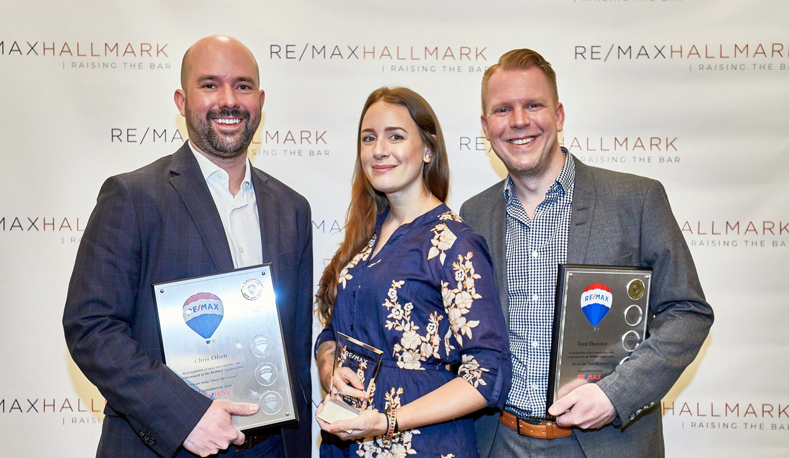 Thurston Olsen Real Estate Team Platinum Club Award RE/MAX. Chris Olsen, Andrea Humeniuk, Ford Thurston pictured holding awards in front of a RE/MAX Hallmark step and repeat backdrop.