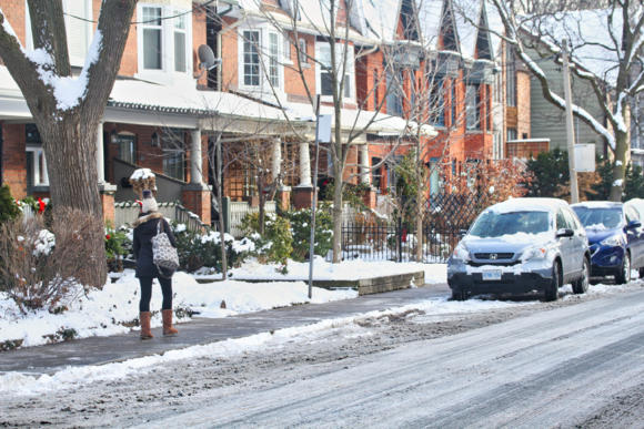 Leslieville, Toronto street with snow on lawns and roof tops. A woman walks along the sidewalk towards a row of parked cars.
